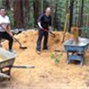 3 women pose with shovels and wheelbarrows behind a pile of sawdust in a forest