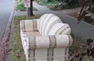 A cushionless sofa sits next to a sidewalk beside a No Parking sign.