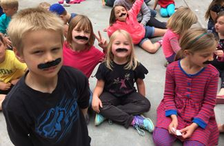 Little boys and girls wear fake moustaches at Arcata's Redwood Day Camp