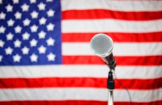 a microphone on a stand in front of the American flag