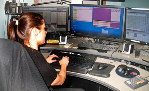 a female Arcata Police Department dispatcher sits before computer screens