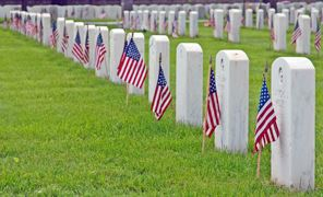 Memorial Day American flags fly in front of gravestones at military cemetery