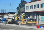 Several men working with heavy equipment on a city street